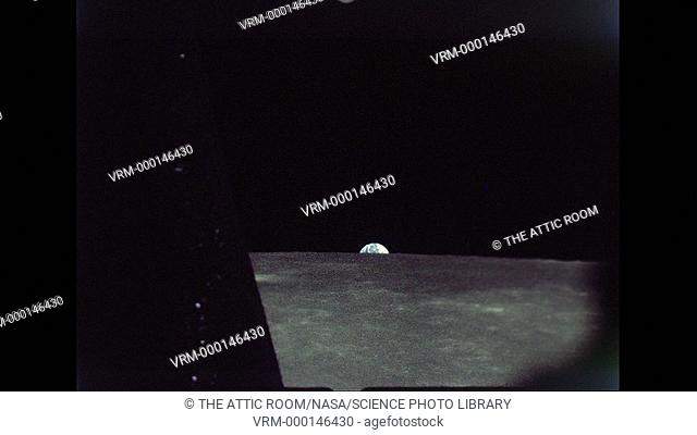 View of the Earth rising above the lunar horizon seen from on board the Command Module Charlie Brown in lunar orbit. Date recorded: 1969-05-22