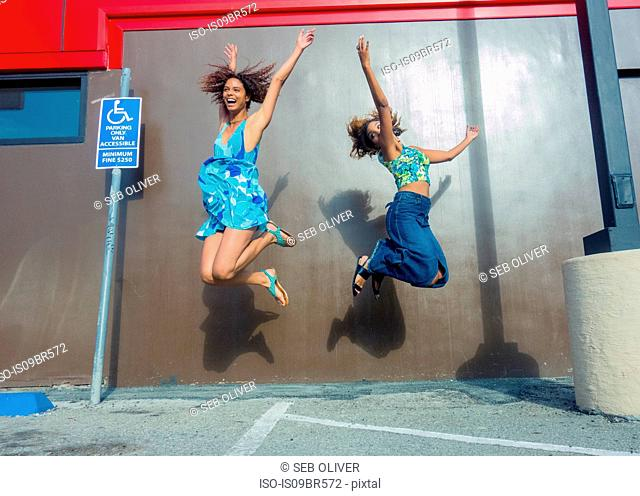 Friends jumping for joy in car park
