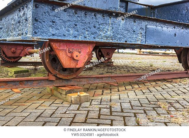 Old and rusting railway wagon with dark blue iron bodyshell and rusting geared wheels used as amobile platform for a small crane, Ayrshire, Scotland