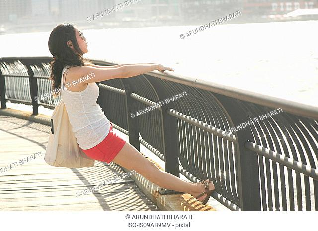 Young woman leaning back on railings looking at river