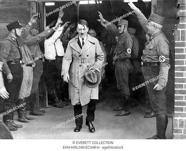 Adolf Hitler, emerging from a Nazi party meeting after a speech, 1930s. He is saluted by uniformed Storm Troopers. Hitler wears a business suit under his trench...