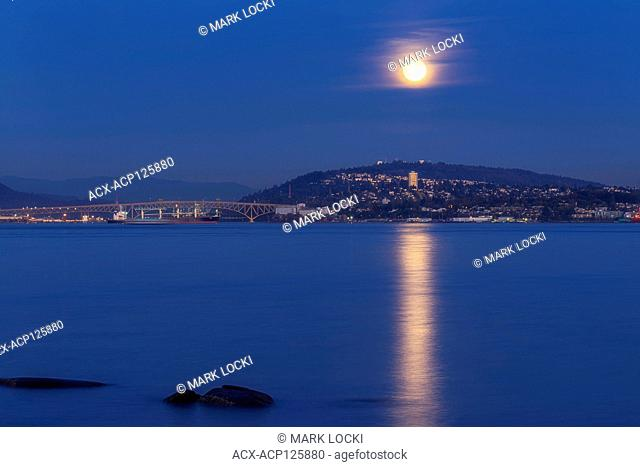The moon rising over Burnaby Mountain as seen from Stanley Park, British Columbia, Canada