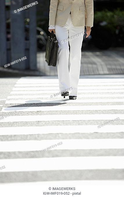 Businesswoman walking on a crosswalk, portrait