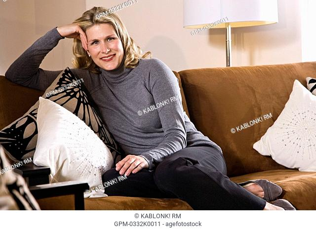 Portrait of mid adult woman relaxing on living room sofa