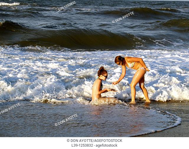 Two Teens-01 are two girls playing in the surf in Kill Devil Hills, NC, USA
