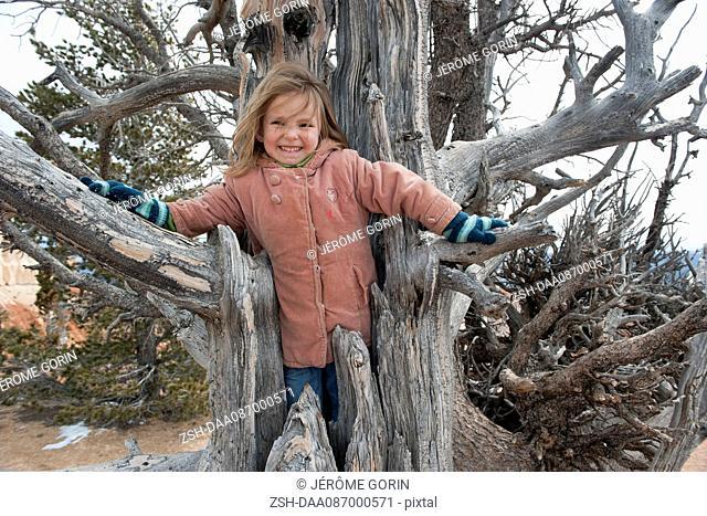 Girl climbing inside dead tree trunk, portrait