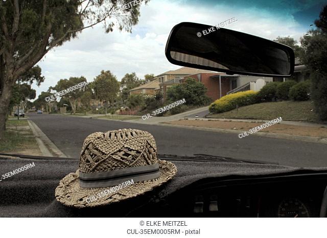 Straw hat sitting on car dashboard