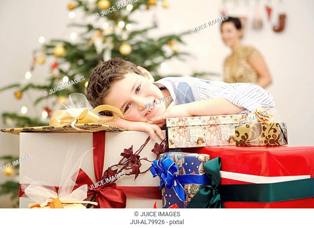 Boy leaning on stack of Christmas gifts
