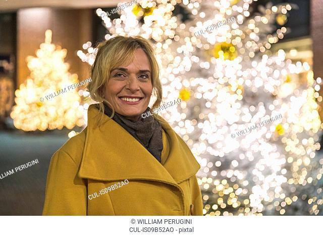 Portrait of mature woman by christmas tree lights at night, Munich, Germany