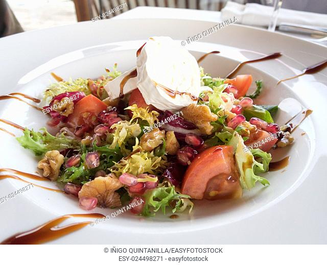 bowl round white plate salad with sliced tomato, lettuce, nut and pomegranate, cheese goat and Modena balsamic vinegar on white tablecloth next to glass and...