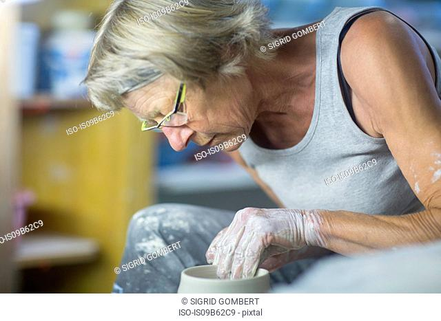 Senior woman in pottery workshop, at potters wheel, making bowl, close-up
