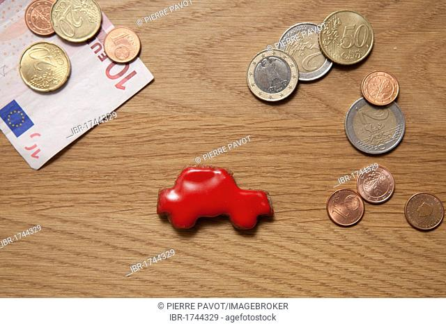 Red car biscuit beside coins and a banknote