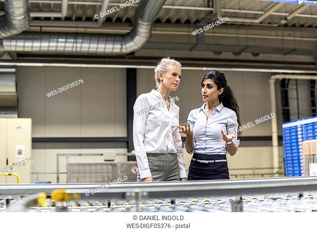 Two women discussing at conveyor belt in factory
