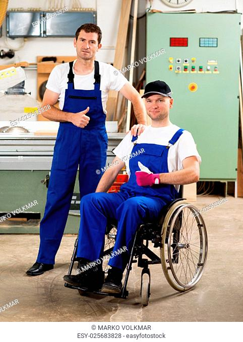 disabled worker in wheelchair in a carpenter's workshop with his colleague with thumb up