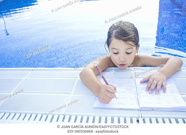 Child girl doing holidays homework over swimming poolside. Summer homework concept for children