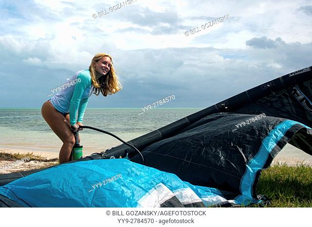 Young woman inflating kite at Veterans Memorial Park - Little Duck Key, Florida, USA