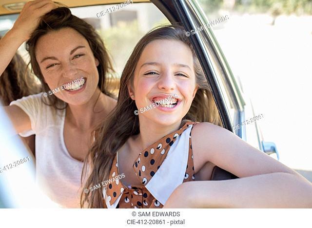 Sisters laughing in car backseat