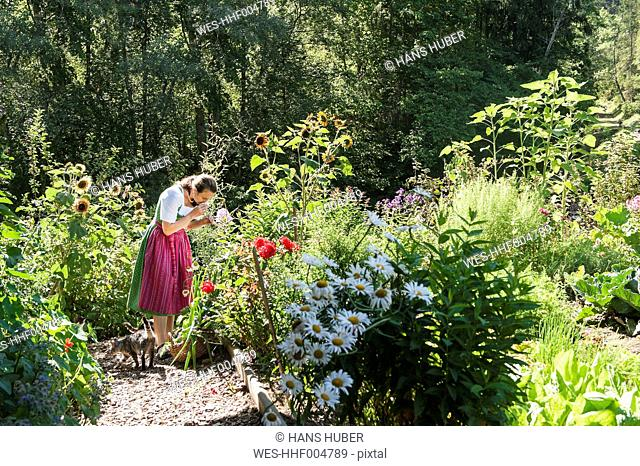Austria, Altenmarkt, Farmer's woman smelling flowers
