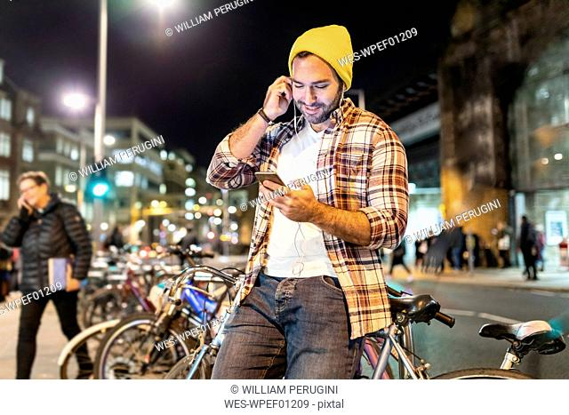 UK, London, man commuting at night in the city and looking at his phone