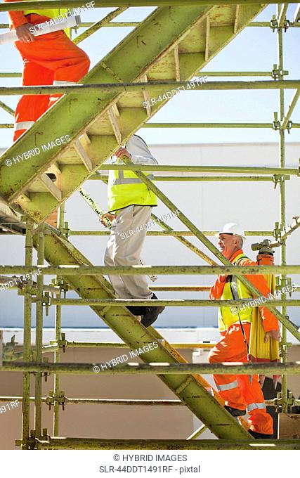 Workers climbing steps on site