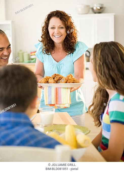 Smiling woman serving family dinner