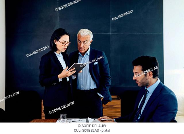 Businessman and woman looking at digital tablet in boardroom