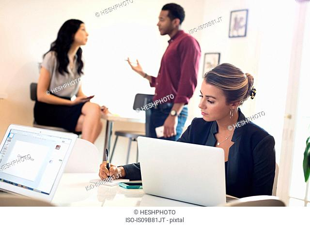 Businesswoman using laptop and making notes at desk