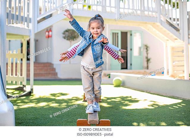 Girls at preschool, portrait balancing on balance beam in garden