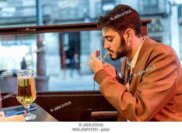 Young man smoking a cigarillo at outdoor bar