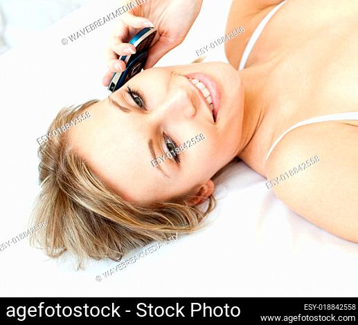 Charming woman talking on phone lying on a bed