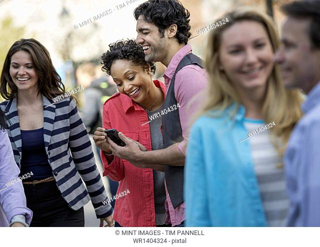 People outdoors in the city in spring time. A group of men and women, two looking at a cell phone screen and laughing