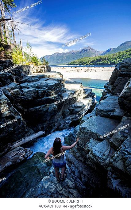 A young woman looks out onto a sand bar from lower Myra Falls at the head of Buttle Lake in Strathcona Park. Vancouver Island, British Columbia, Canada