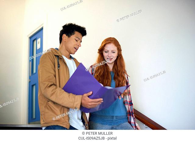 Young male and female college students moving down stairway reading file