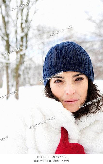 Woman in snowy woods looking to camera