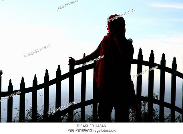 A girl holds a fence at Nilgiri Hill which is located 47 kilometers Southeast of Bandarban town on Chimbuk range, at a height of 2400 feet above sea level...