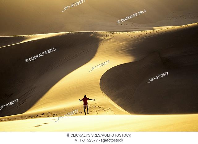 Boy has fun running down a dune in the desert,Walvis Bay,Namibia,Africa