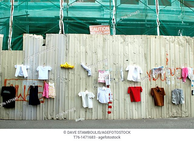 funny place to hang laundry next to warning sign and construction site in Georgetown, Penang, Malaysia