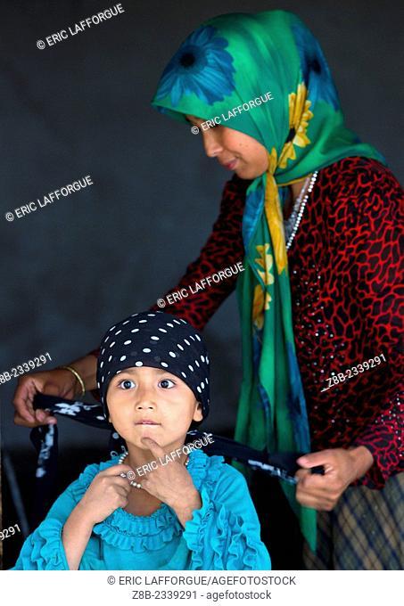 Uyghur Woman Tying Her Daughter Scarf, Xinjiang Uyghur Autonomous Region, China