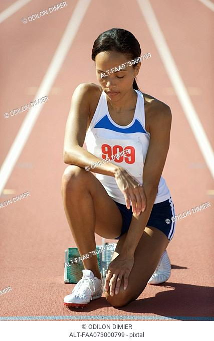 Female runner crouching at starting line with eyes closed