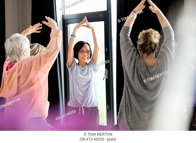 Active seniors exercising in circle, stretching arms