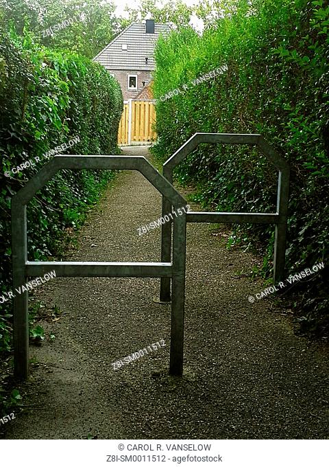 Small pathway in residential area in Limburg in the Netherlands. The barriers are so that you must get off your bicycle and walk on this path