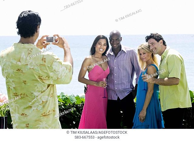 Man taking a group photo of people at the beach