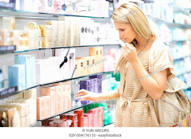 A young woman going to pick up a bottle of perfume while smelling a tester