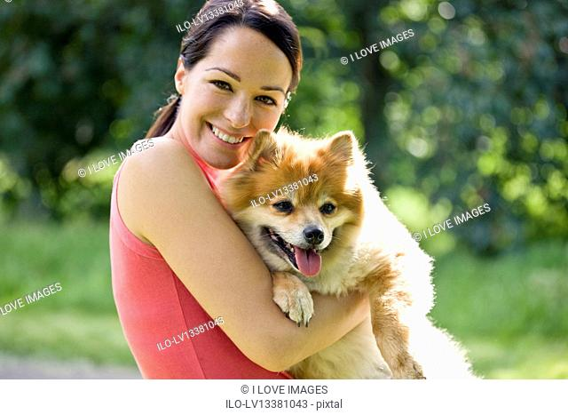 A young woman outdoors, holding her dog