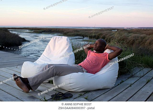 Man relaxing on dock at water's edge