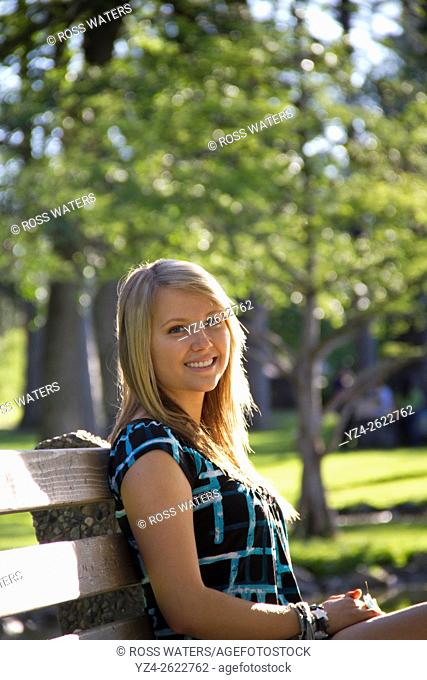 A young woman sitting outdoors at a park in Spokane, Washington, USA