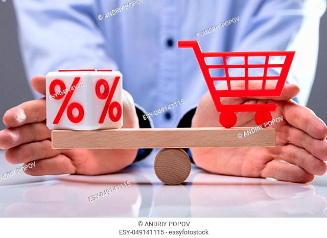Human's Hand Protecting Balance Between Red Percentage Cubic Block And Shopping Cart On Wooden Seesaw
