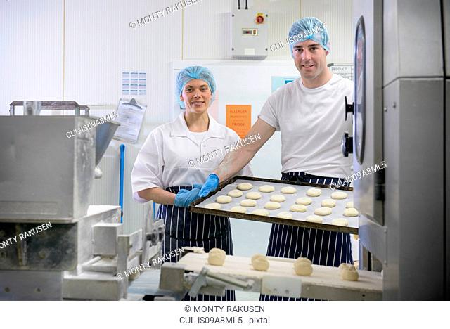 Bakers holding tray of prepared dough, portrait