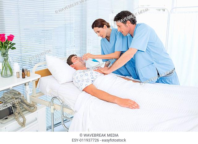 Worried doctors doing heart massage and holding oxygen mask