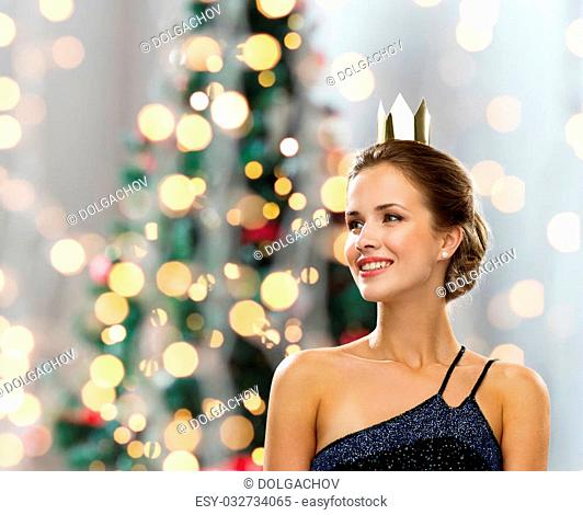 people, holidays, royalty and glamour concept - smiling woman in evening dress wearing golden crown over christmas tree lights background